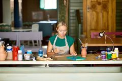 Blonde Young Woman Painting in Art Studio stock photos