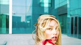 Portrait of pretty blonde woman with red lipstick in red dress dancing outside. With modern buildings on background. caucasian female outdoors in urban stock video