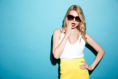 Portrait of a pretty blonde woman wearing sunglasses and posing. Isolated over blue background Royalty Free Stock Image