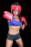 Portrait of pretty boxer with fighting stance. Against black background royalty free stock photos