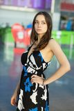 Portrait of pretty brunette. Posing standing at the airport wearing a dress royalty free stock images