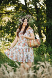 Portrait of pretty brunette woman with long hair and wrath of wildflowers on head, holding basket in hand. Girl wearing dress in f Stock Photos