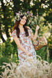 Portrait of pretty brunette woman with long hair and wrath of wildflowers on head, holding basket in hand. Girl wearing dress in f Stock Images