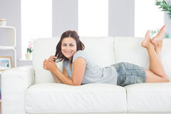 Portrait of pretty brunette woman lying on her couch in the living room Stock Image