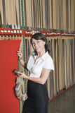 Portrait of pretty businesswoman holding thin veneer sheet and samples Stock Photos