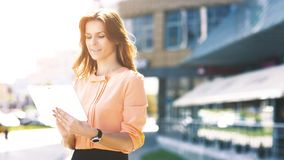 Portrait of pretty businesswoman smart casual using digital tablet outdoors Stock Images
