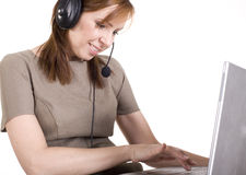 Portrait of pretty call operator smiling and typing on lap top. Isolated Stock Image
