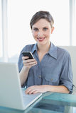 Portrait of pretty calm businesswoman holding her smartphone sitting at her desk Stock Images