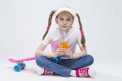 Portrait of Pretty Caucasian Blond Girl wearing Visor Sitting on Floor with Cup of Juice. Kid Ideas and Concepts. Portrait of Pretty Caucasian Blond Girl wearing Stock Photo
