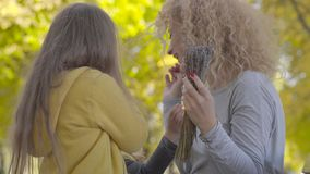 Portrait of pretty caucasian woman smelling flowers given to her by two cute little girls. Daughters surprising their stock footage