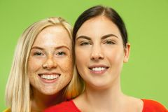 Portrait of pretty girls isolated on green studio background royalty free stock images