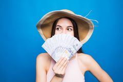Portrait of pretty charming woman covering closing half face with fan from dollars looking out with eyes at camera isolated on blu stock photography