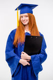 Portrait of pretty cheerful girl in gown and graduation cap Stock Photos