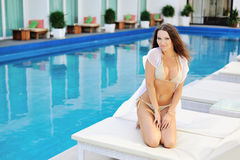 Portrait of pretty cheerful woman posing at the luxury poolside Royalty Free Stock Photography