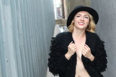 Portrait of pretty cheerful woman wearing black fur dress and modern hat in cold weather day. Walking outdoors in the winter. And smiling royalty free stock image