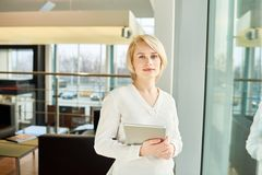 Portrait of Pretty Confident Entrepreneur. Waist-up portrait of confident young entrepreneur with digital tablet in hands looking at camera while standing at Stock Photography