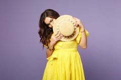 Portrait of pretty confused young woman in yellow dress covering face with summer hat  on pastel violet royalty free stock images