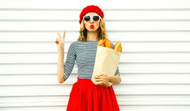 Portrait pretty cool girl wearing french red beret holding paper. Bag with long white bread baguette on white wall background stock photos