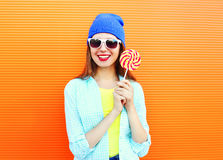 Portrait pretty cool smiling woman and lollipop over colorful orange Stock Images