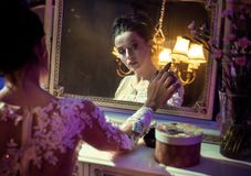 Portrait of a pretty countess touching an antique mirror. Portrait of a pretty, brunette countess touching an antique mirror royalty free stock images