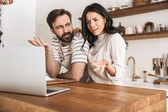 Portrait of pretty couple looking at laptop while cooking pastry in kitchen at home. Portrait of pretty couple men and women 30s wearing aprons looking at laptop stock images