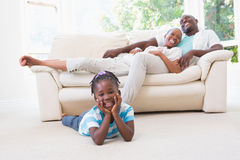 Portrait of a pretty couple sitting on couch and their  daughter looking at camera Royalty Free Stock Photos