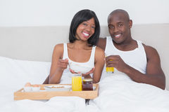Portrait of a pretty couple taking breakfast in bed together Royalty Free Stock Photo