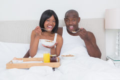 Portrait of a pretty couple taking breakfast in bed together stock photos