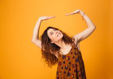 Portrait of a pretty curly haired girl holding copyspace. Isolated over yellow background Stock Image