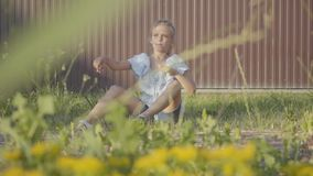 Portrait of a pretty cute little girl launching the small plane sitting on the grass under the fence. The child spending. Portrait of the pretty cute little girl stock footage