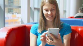 Portrait of pretty dreamy young woman in blue t-shirt sitting in cafe thinking. Using her smartphone. Chatting with friends smiling stock video