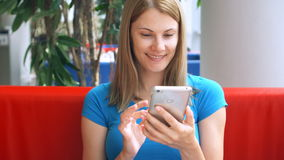 Portrait of pretty dreamy young woman in blue t-shirt sitting in cafe thinking. Using her smartphone. Chatting with friends smiling stock video footage