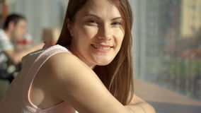 Portrait of pretty dreamy young woman sitting at table in cafe near window thinking looking at camera smiling. Food stock video