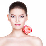 Portrait of pretty face of beautiful woman with a pink rose. Royalty Free Stock Image