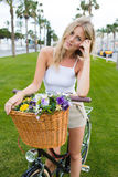 Portrait of pretty face young woman standing in the park with her classic bicycle and looks at the camera Royalty Free Stock Photos
