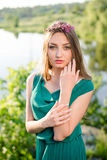 Portrait of pretty fairy: young beautiful lady having fun posing in green dress with pink wreath of flowers & sun light rays Stock Images