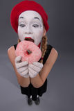 Portrait of pretty female mime eating a tasty pink Royalty Free Stock Photography
