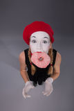 Portrait of pretty female mime eating a tasty pink Royalty Free Stock Images