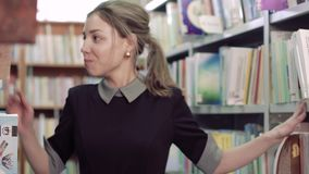 Portrait of pretty female student in library looking for a book. Portrait of pretty female student walking along bookcases in library and looking for a book stock video footage
