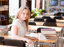 Portrait of a pretty female student studying in library Stock Image