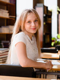 Portrait of a pretty female student studying in library Royalty Free Stock Images