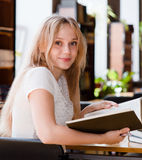 Portrait of a pretty female student studying in library with open book royalty free stock photo