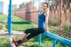 Portrait of Pretty fit girl in a blue shirt and leggings with ideal body sits on the railing in the outdoor gym. stock photo