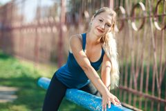Portrait of Pretty fit girl in a blue shirt and leggings with ideal body in sport place. stock photography