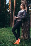 Portrait of pretty fit sportswoman wearing tracksuit leaning against tree listening to music in earphones holding sports. Water bottle standing in forest Stock Image