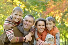 Pretty friendly family. Portrait of pretty friendly family in autumnal park Royalty Free Stock Photography