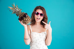 Portrait of a pretty funny summer girl in sunglasses. Holding and pointing at pineapple in her hands  over blue background Stock Image