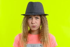 Portrait of a pretty funny teen girl with a pensive face, blonde girl with curly hair in hat with thoughtful expression, presses stock image