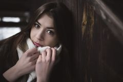 Portrait of pretty girl with hands close to her face on scarf. Cold winter season. Interior of abandoned house or shed from dark royalty free stock image