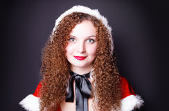 Portrait of a pretty girl dressed as Santa against Stock Images
